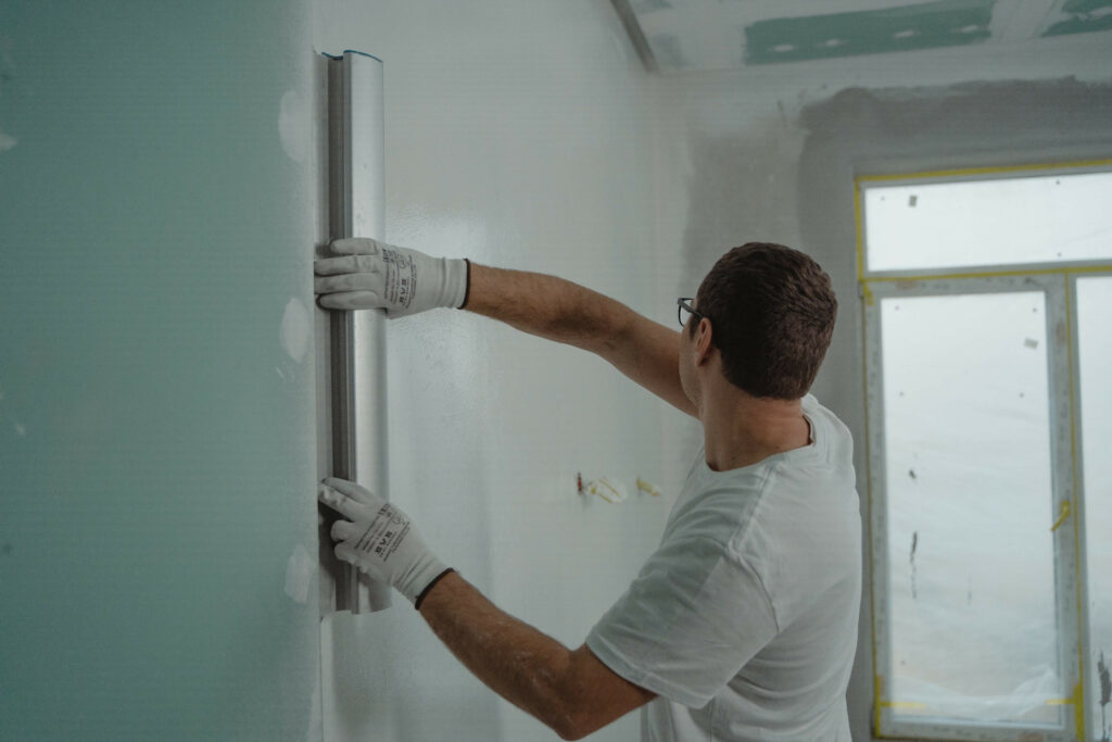 Professional painter levelling off a wall before plastering and painting